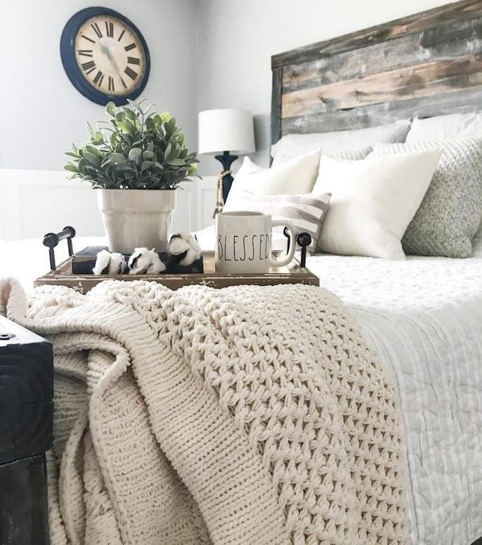 linge de lit gris, blanc et beige avec une tete de lit en planches de bois brut, couverture de lit plaid à grosses mailles, table de service eustique, horloge vintage sur mur blanc