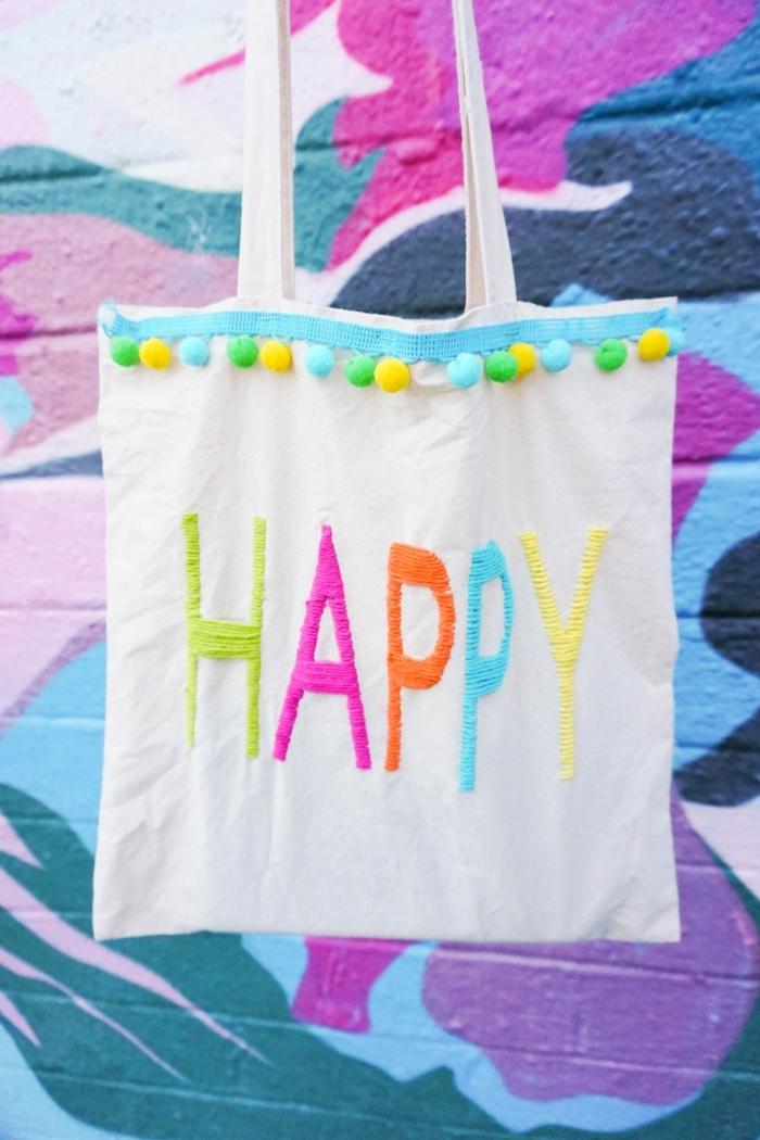 décorer un tote bag blanc avec broderie aux mots happy et bordure en petits pompons, modèle sac à main customisé