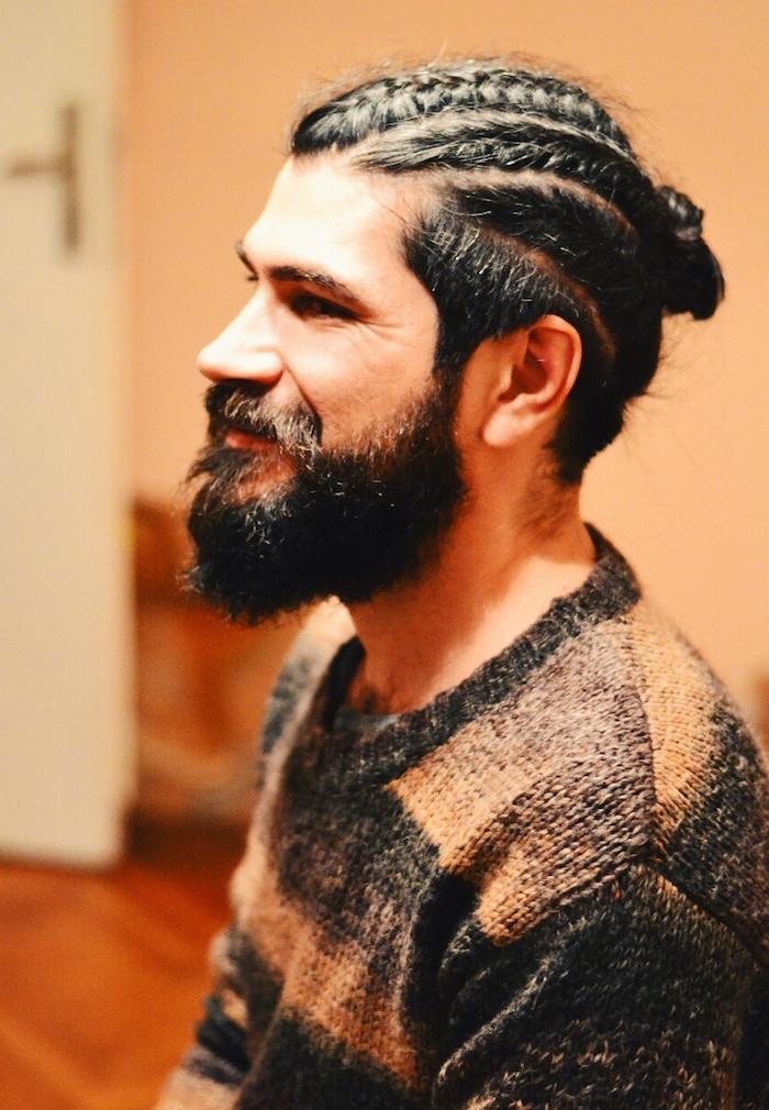 coiffure avec tresse plaquée en chignon pour homme blanc avec barbe style hipster