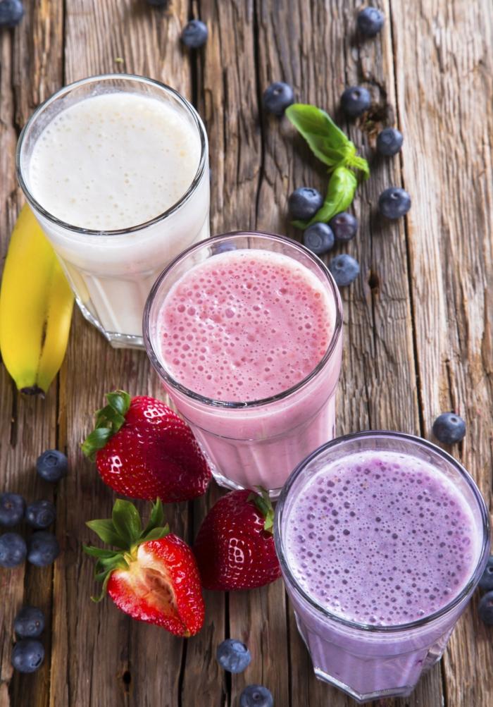 milkshake facile et délicieux avec des fruits fraîches et du lait, bananes, fraises, baies, planches en bois brut