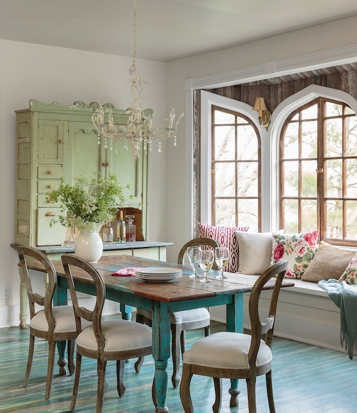 parquet bois repeint en bleu, canapé blanc décoré de coussins colorés, chaises bois tapissées, vaisselier vert pastel, lustre original