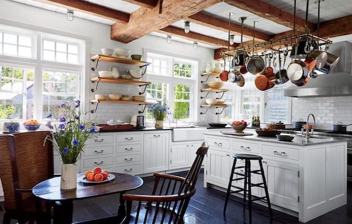 ustensiles de cuisine suspendus, ilot central blanc, parquet noir bois, étagères bois et métal, carrelage metro blanc, poutres apparentes