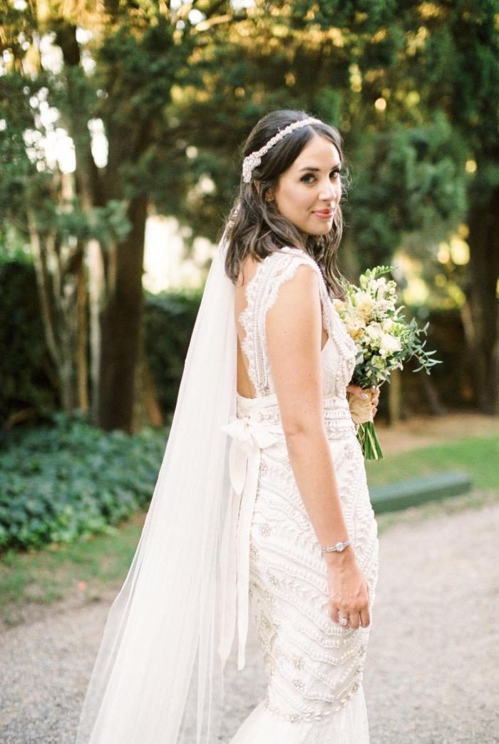 une jolie robe de mariée d'inspiration années 20 avec son incrustation de perles pour avoir un look à la fois rétro chic et glamour le jour j