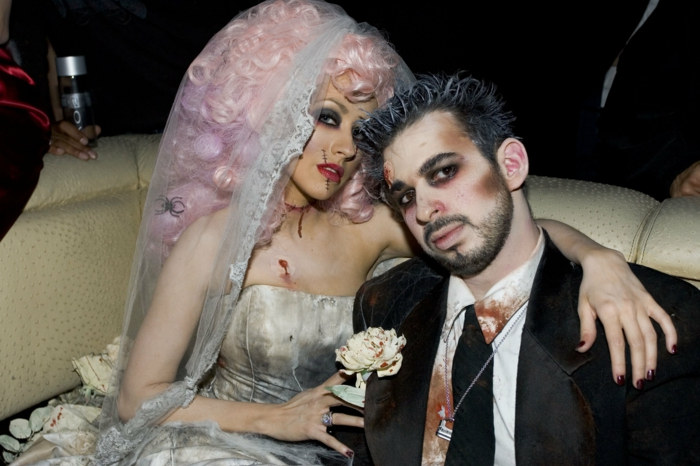 Christina Aguilera en robe de mariée, robe bustier, voile long, perruque rose, costume et cravate noirs, chemise blanche tachée de sang