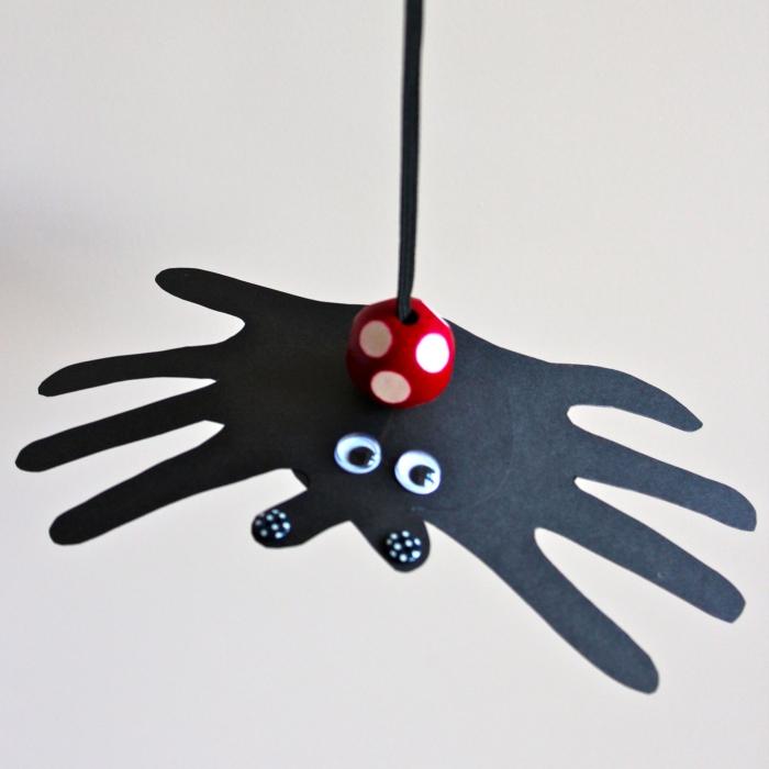 idée d'activité manuelle facile et rapide sur le thème d'halloween pour amuser les enfants, araignée empreinte de main en papier avec balle qui rebondit