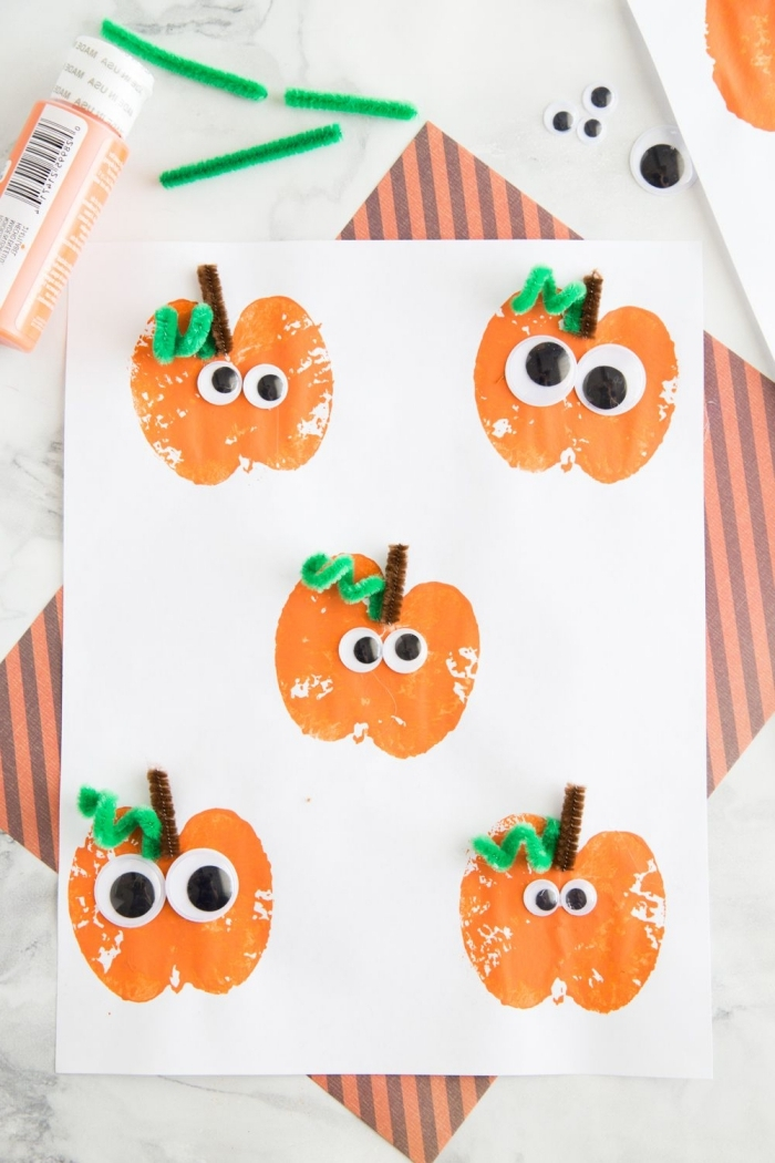 une activité halloween de maternelle pour réaliser une peinture originale d'empreintes de pommes décorées façon citrouilles d'halloween mignonnes