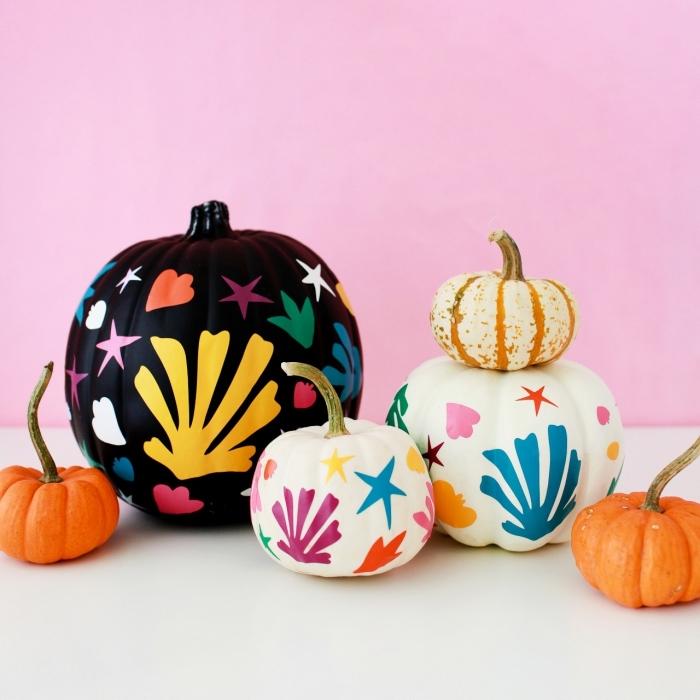 idée pour faire une citrouille d halloween, modèle de citrouille peinte en noire avec dessins colorés, idée objet facile DIY pour enfants