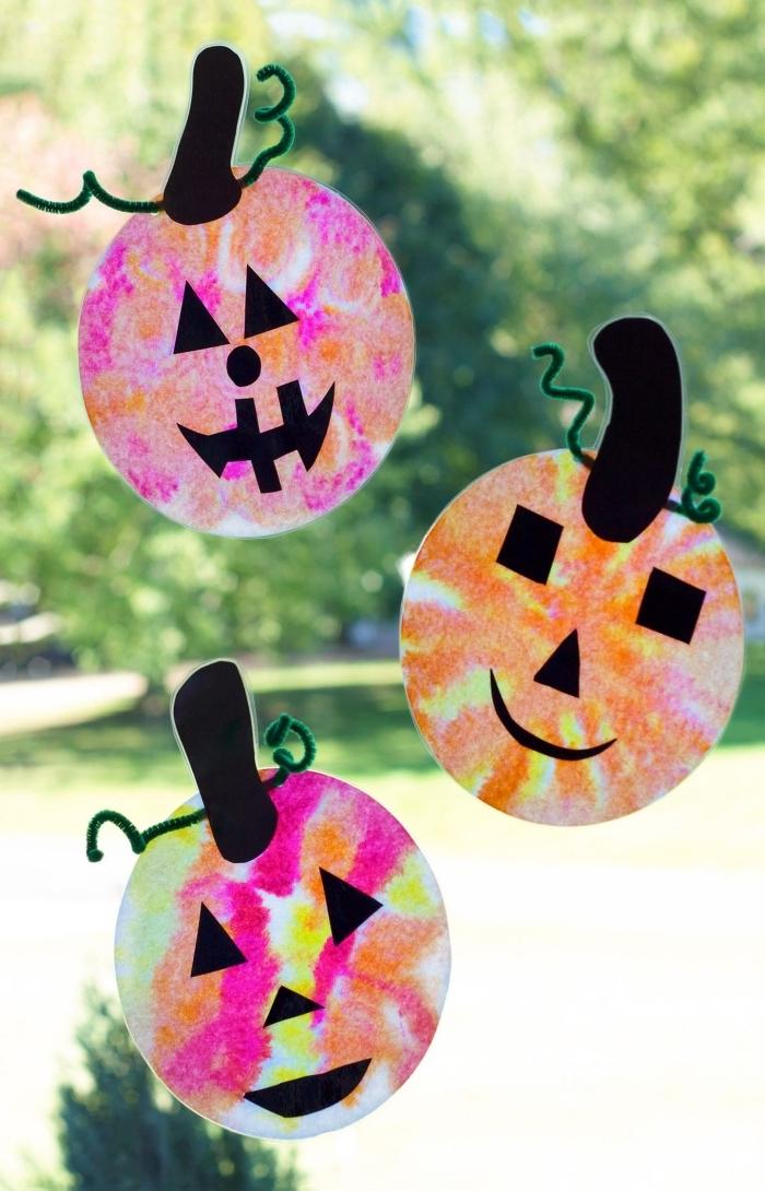 activité manuelle maternelle spécial halloween, des attrape-soleil en forme de la citrouille jack o'lanterne à coller à la fenêtre