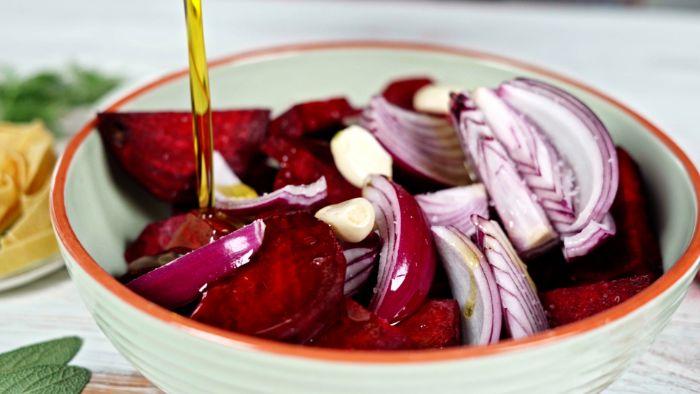 ajouter de l huile dans bol de betterave aux oignons rouges et gousses d ail idee repas halloween aux pâtes