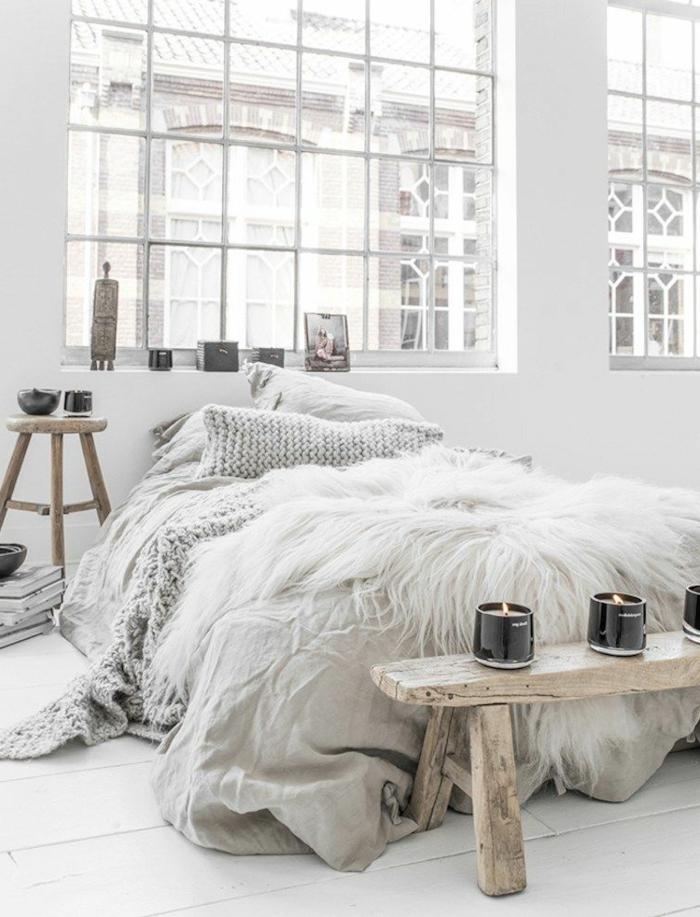 jolie deco cocooning dans une chambre, banquette en bois brut, tabouret en bois, grandes fenêtres d'artiste, bougeoirs, plaid tricoté
