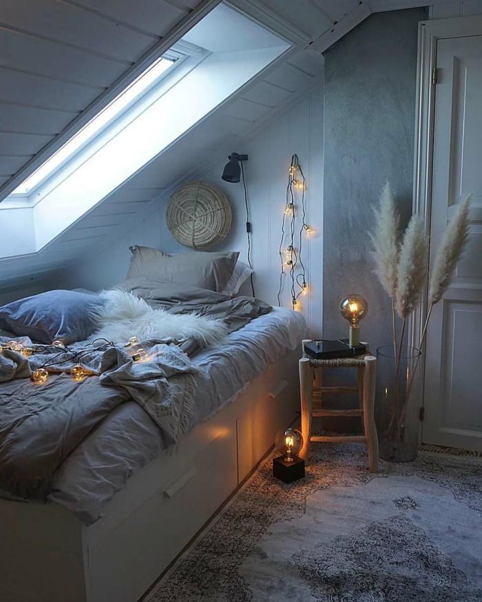 chambre cosy, ambiance cocooning, lit gris accueillant, guirlande lumineuse, fenêtre sous pente, grand vase avec fleurs séchées