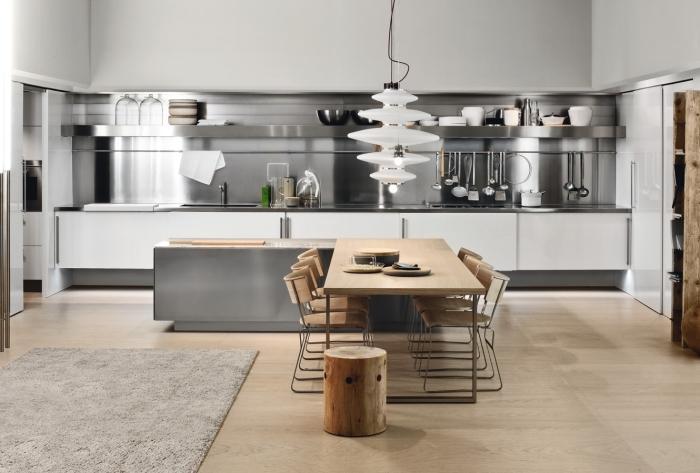 modèle de cuisine moderne au parquet bois et murs blancs aménagée avec îlot central en L et crédence en inox