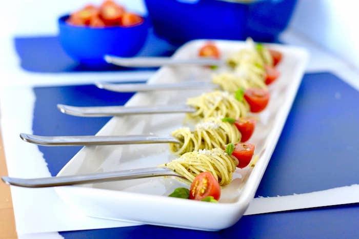 idée de pâtes sauce pesto enroulées sur une forchettes avec tomate cerise et basilic et servis dans une assiette blanche, apéritif diner raffiné