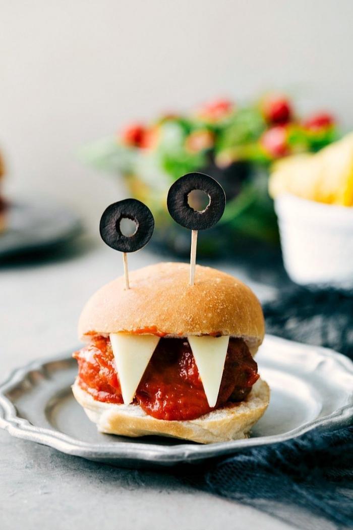repas d'halloween original pour petits et grands, recette de burger monstre vampire aux boulettes de viande et sauce marinara avec des olives coupées en yeux