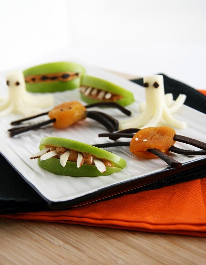 des amuses-bouches d'halloween faciles et rapides réalisés avec des tranches de pommes et des fruits séchées, des dents de vampire à la pomme et des abricots secs en araignées