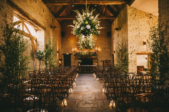 grange rénovée et décorée pour un mariage rustique, plusieurs chaises rustiques, chandeliers en fleurs