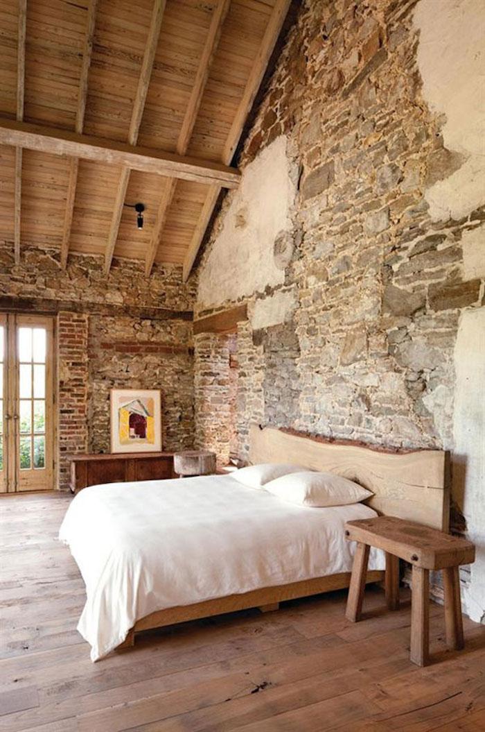 chambre dans grenier de vieille maison avec murs en pierres apparentes et charpente sol et lit en bois