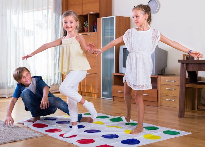 comment jouer le twister, idée d activité anniversaire, jeu d adresse amusante avec une toile à cercles colorés