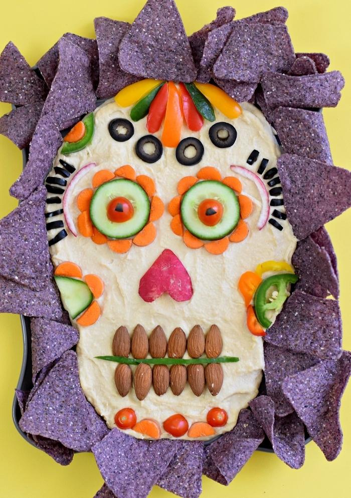 recette de houmous d'halloween fait-maison décorés avec des morceaux de légumes, d'amandes et d'olives pour former une tête de mort mexicaine