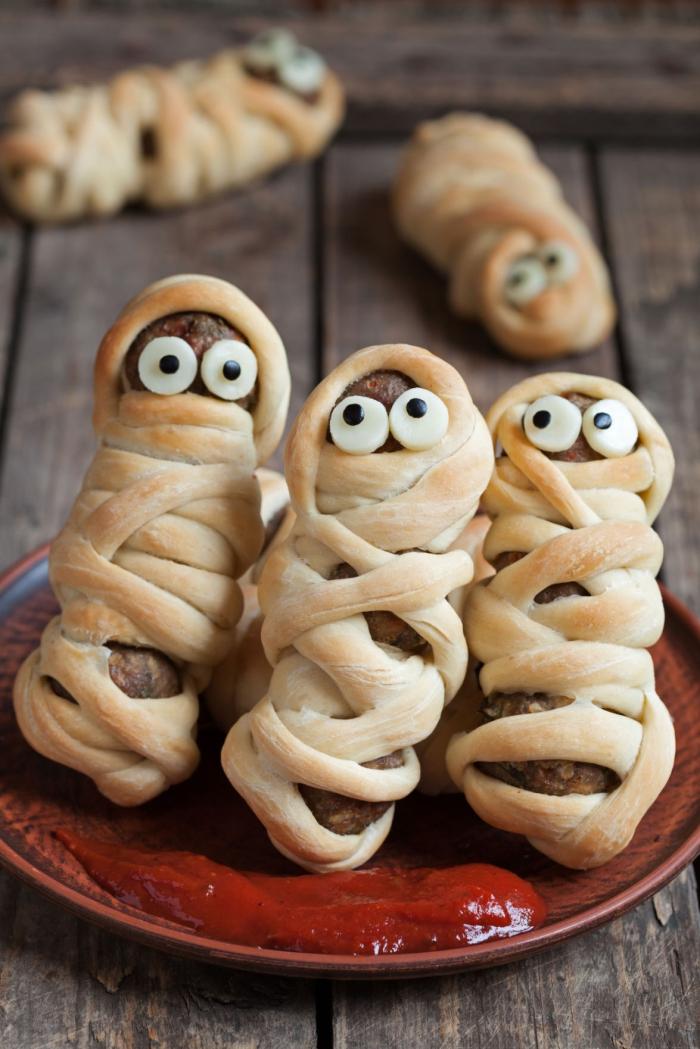 recette effrayante et rigolote pour un apero dinatoire halloween, des saucisses grillées enrobées de pâte feuilletée façon petits momies