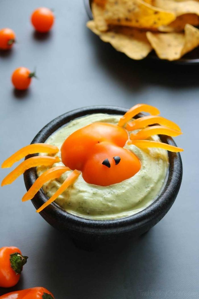 sauce dip à l'avocat spécial halloween décorée avec une araignée en poivron rouge, trempette d'halloween pour un apéro dînatoire ou un goûter d'anniversaire thématique