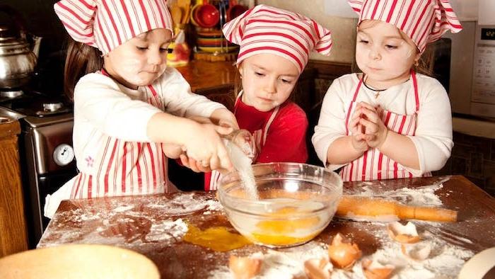 premier cours de cuisine des enfants vêtus comme des chefs de restaurant qui fond la cuisine, patisserie enfant