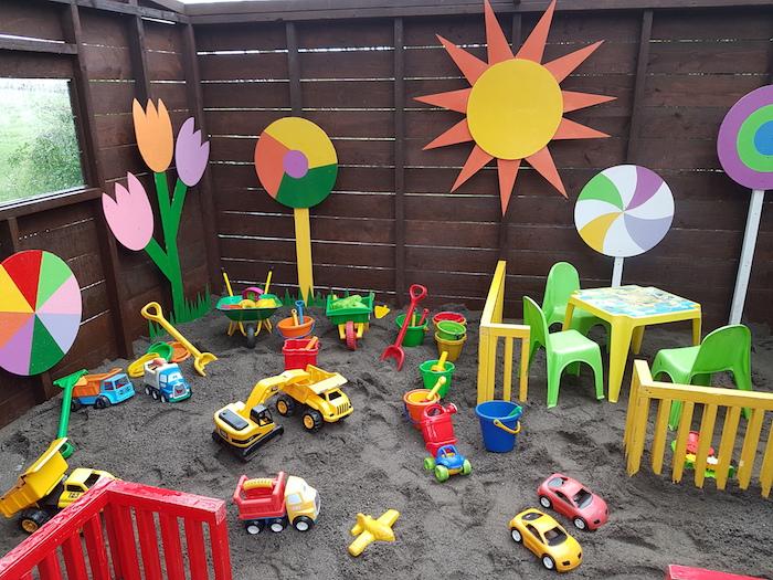 organiser un anniversaire en plein air, un grand bac à sable dans un air de jeu, jouet voiture et autres moyens de transport, décor enfant coloré en papier cartonné, table et chaises enfant