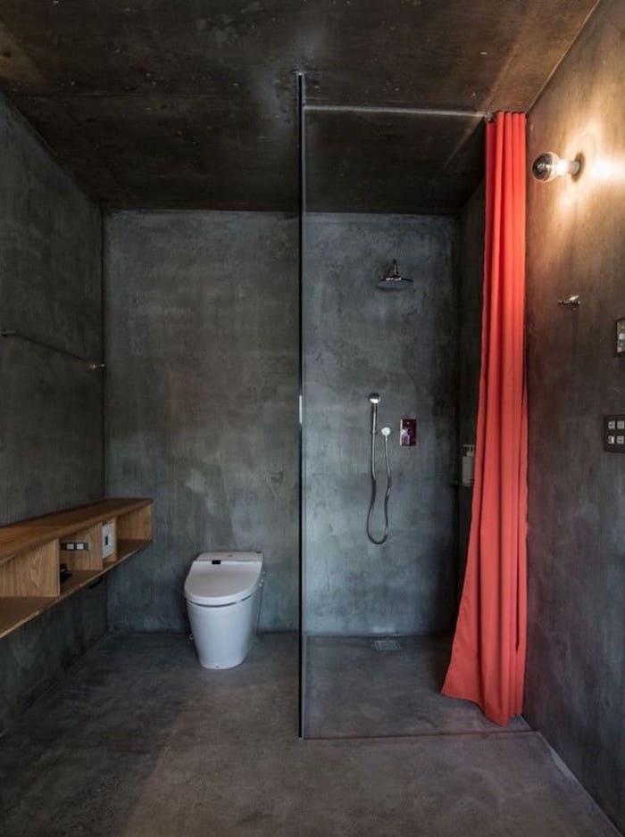 petite salle de bain fermé avec revêtement ciment gris foncé sol murs avec douche italienne en monobloc