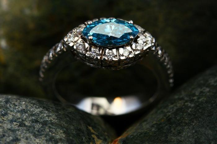 jolie bague avec pierres incrustées, pierre précieuse bleue, plusieurs petites pierres incrustées