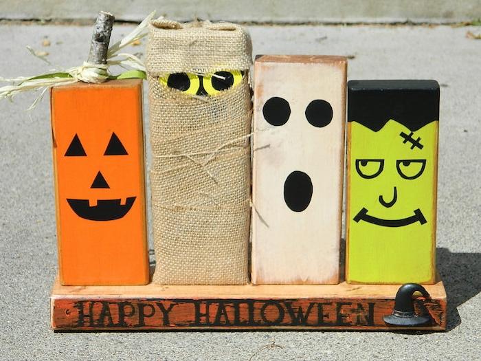 modele deco halloween a faire soi meme, blocks en bois décorés à motif monstre, momie, jack o lantern sur une planche de bois