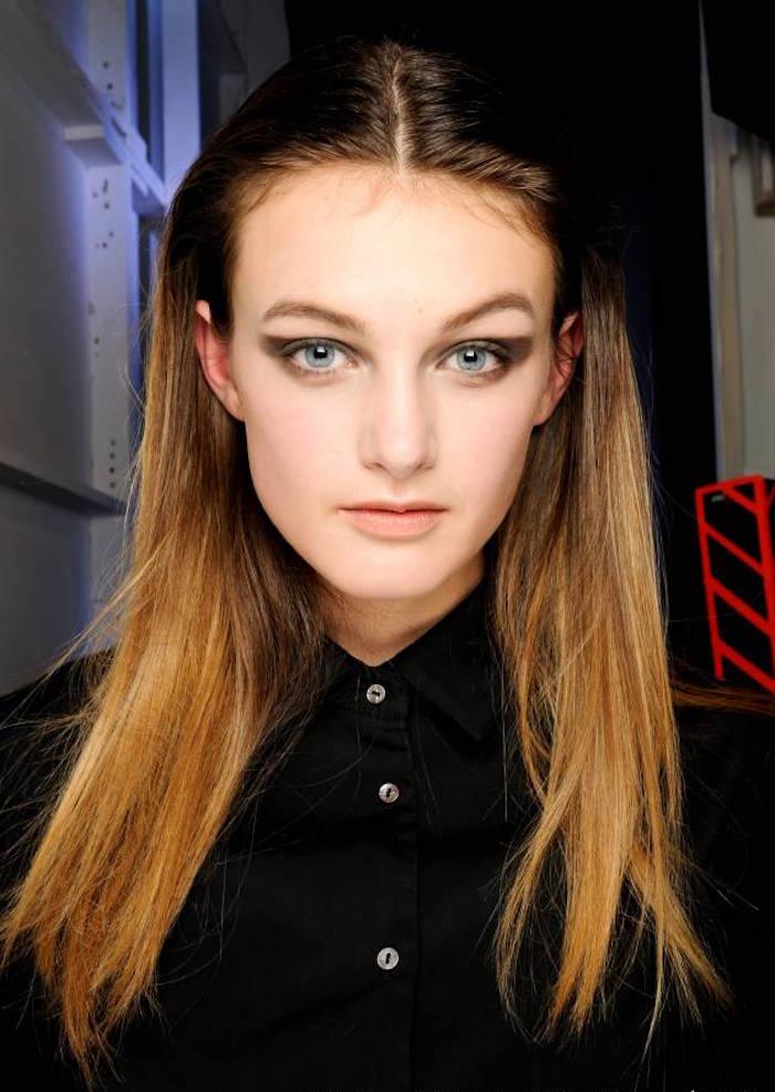 tie and dye couleur blond caramel sur cheveux foncé chatain brun raides sur femme aux yeux bleus et chemise noire