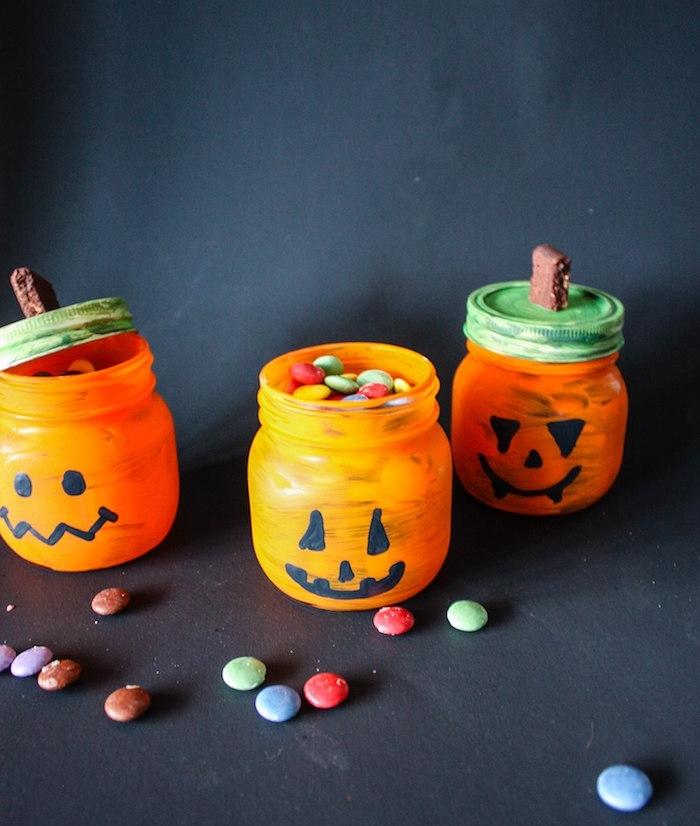 recyclage pot en verre décoré de peinture orange avec dessin motif jack o lantern à l indélébile noir, rangement bonbons et vase