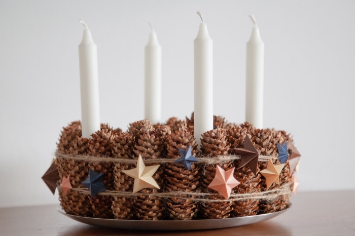 accessoire de table de Noel original et facile à réaliser soi-même, modèle de bougeoir en pommes de pins avec déco à petites étoiles