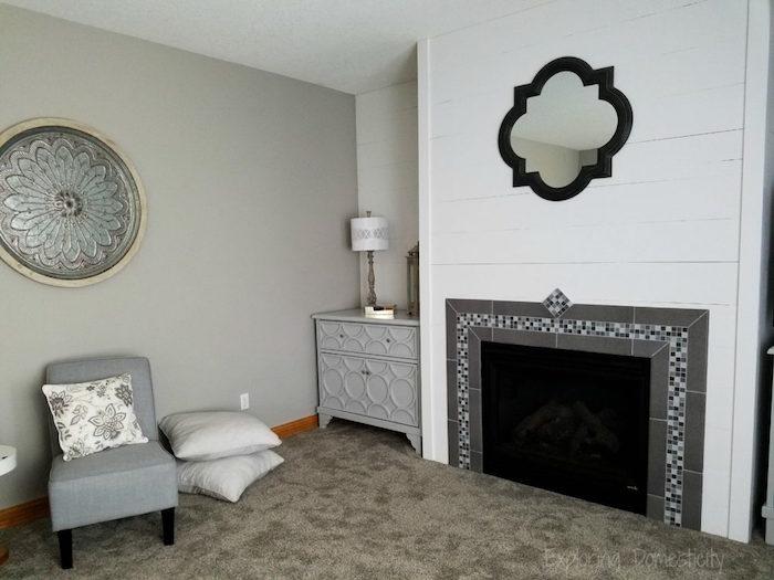 manteau cheminée en carrelage gris et mosaique style credence sur mur en bois blanc dans salon avec moquette taupe et plat arabe en métal sur le mur gris