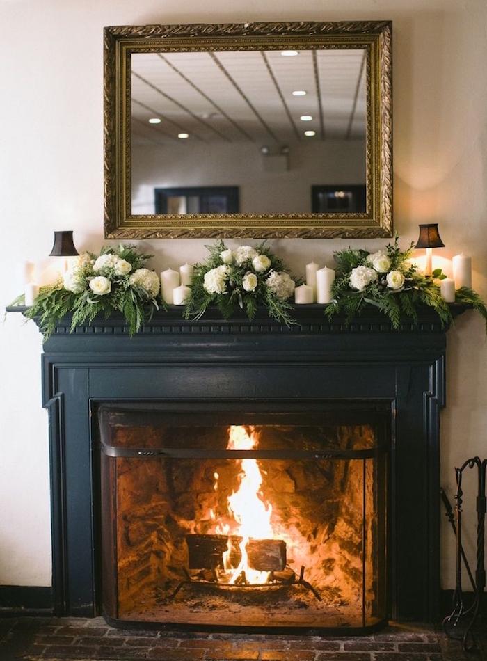 décoration cheminée avec manteau noir mat sur mur blanc, bouquets roses blanches et miroir au cadre doré