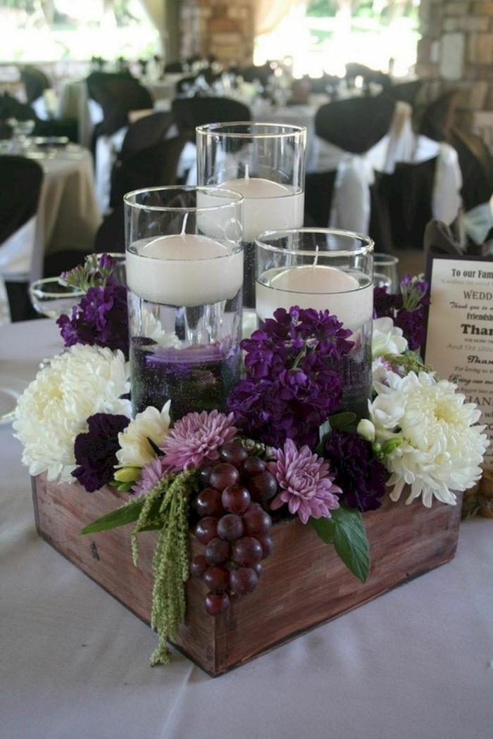 bougeoirs en verre avec bougies flottantes, fleurs rustiques et vigne dans une petite caisse de bois