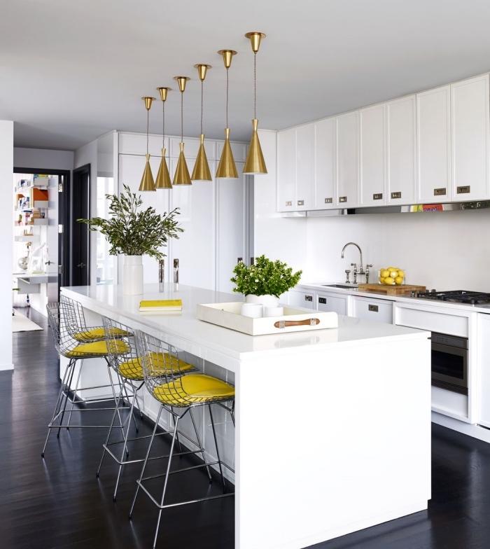 cuisine blanche avec objets en argent et or, déco de style moderne dans une cuisine ouverte avec ilot central