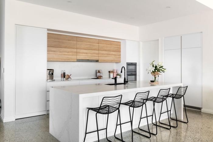 design intérieur épuré dans une cuisine blanche avec îlot à évier noir mate et chaises de bar en noir, idée déco moderne