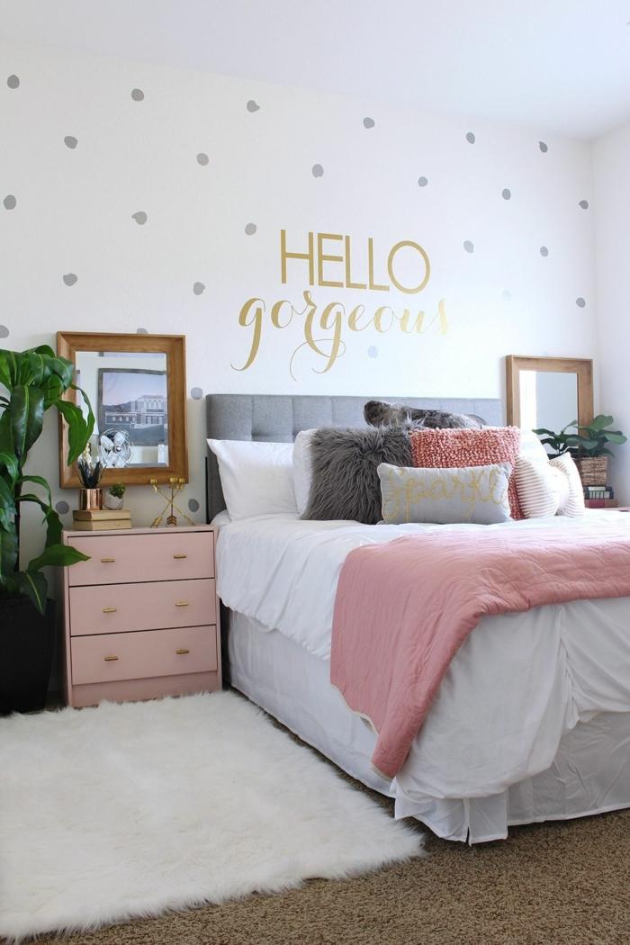 peinture murale blanche, commode tiroirs rose, peinture au cadre doré, script au mur, coussins moelleux