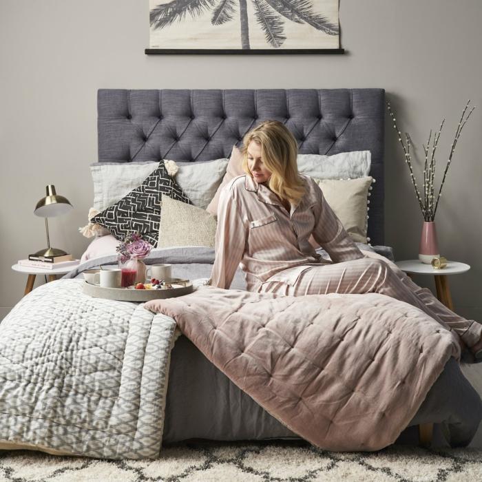 édredon rose cendré et tapis berbère dans une chambre cocooning, femme dans son lit, deux tables de chevet rondes