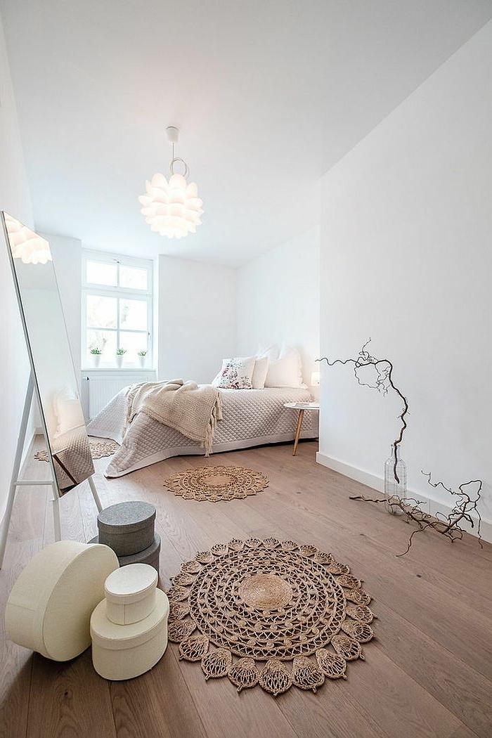 tapis macramé, murs blancs dans une grande chambre cosy, miroir rectangulaire, plafonnier blanc