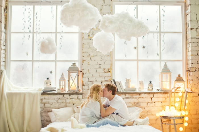 lit cocooning, lampes nuages, lanternes grecques, mur en briques blanches, chaise vintage, un couple