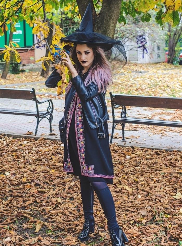 déguisement sorcière femme en chapeau noir, robe et blouson noir, bottes noires, maquillage avec rouge à lèvres noir
