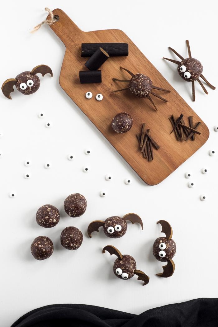 des chauves-souris en boules d'énergie avec des ailes découpées dans du chocolat, recette santé de bouchées d'halloween aux dattes, flocons d'avoine et beurre de cacahuète
