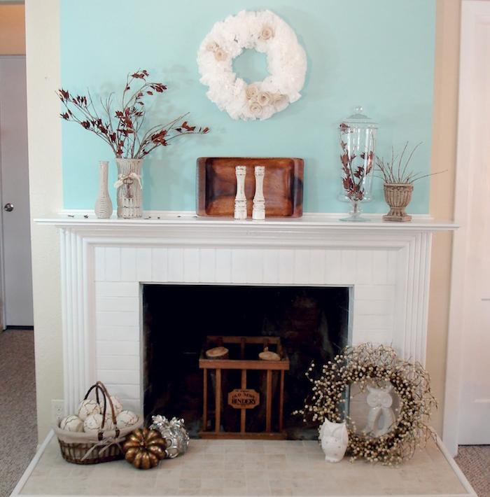 cheminée blanche sur mur turquoise avec déco automnale feuilles mortes et couronnes fausses fleurs blanches