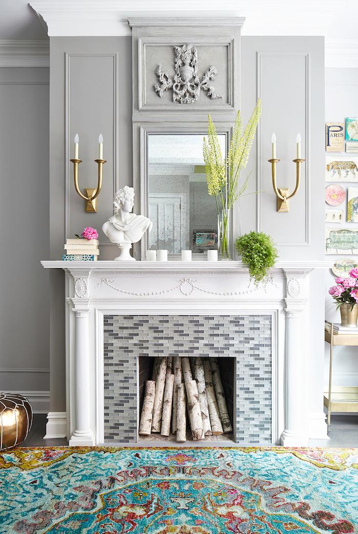 déco cheminée moderne classe rénovée avec manteau blanc sculpté crédence et mur gris clair avec objets déco statuette torche electrique, tapis turquoise de salon