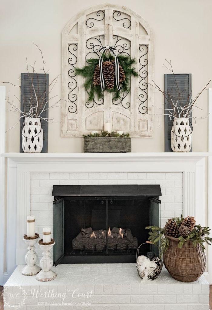 décorer cheminée en hiver avec pommes de pin, bougies, vases, brindilles, déco symétrique