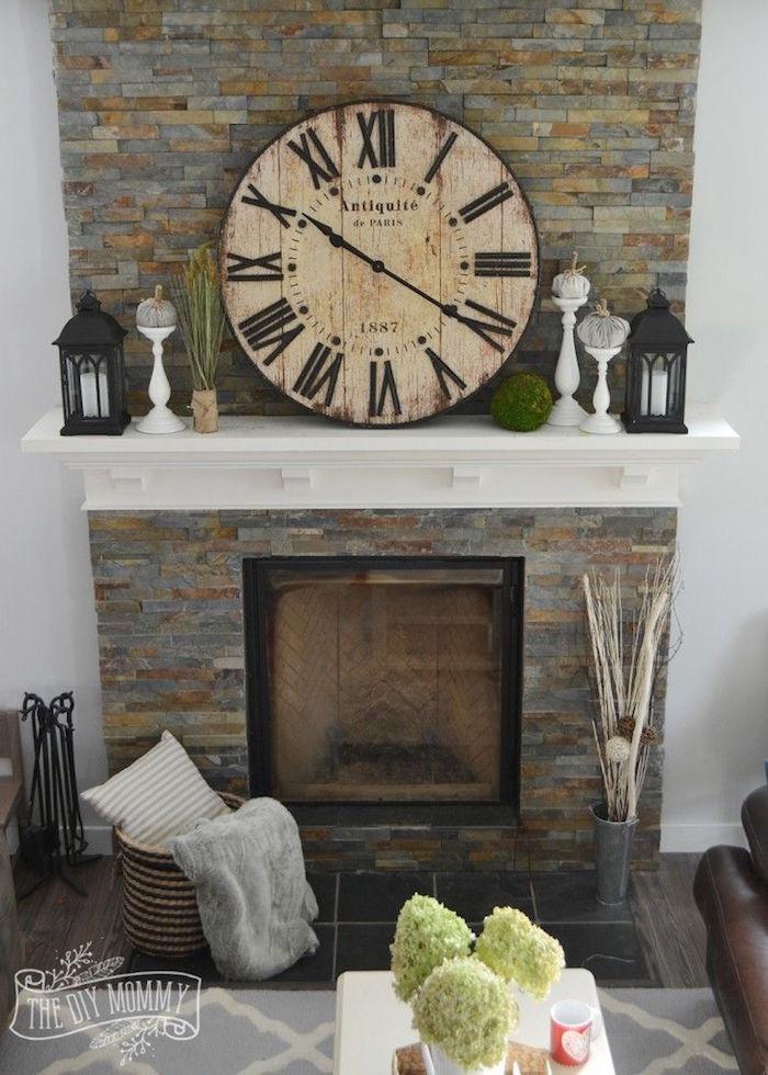 idée déco de cheminée avec manteau en plaquette de pierre de parement avec etagere blanche et objets decoration avec horloge ancienne retro