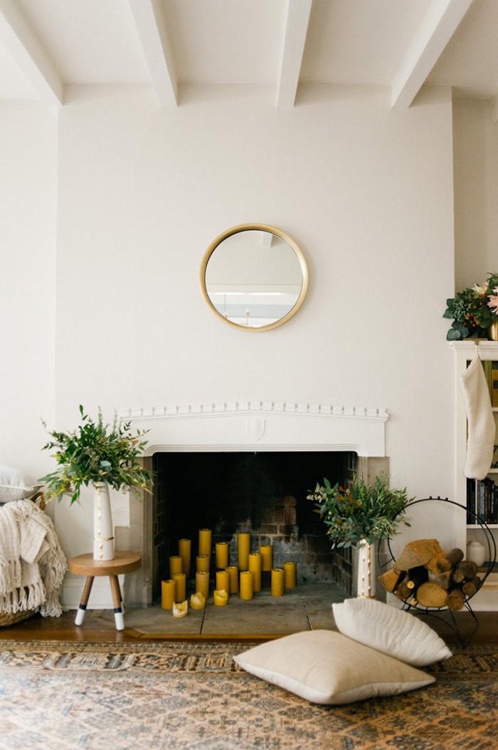cheminée encastrée dans mur blanc avec manteau sculpté minimaliste avec bougies jaunes dans foyer et miroir circulaire or vintage