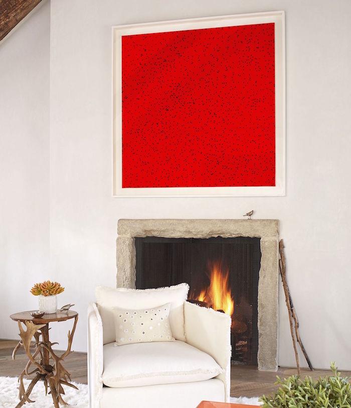 manteau de cheminée simple en pierre sur mur blanc et déco avec cadre abstrait rouge à pois et sol à parquet avec fauteuil blanc et table basse en bois design